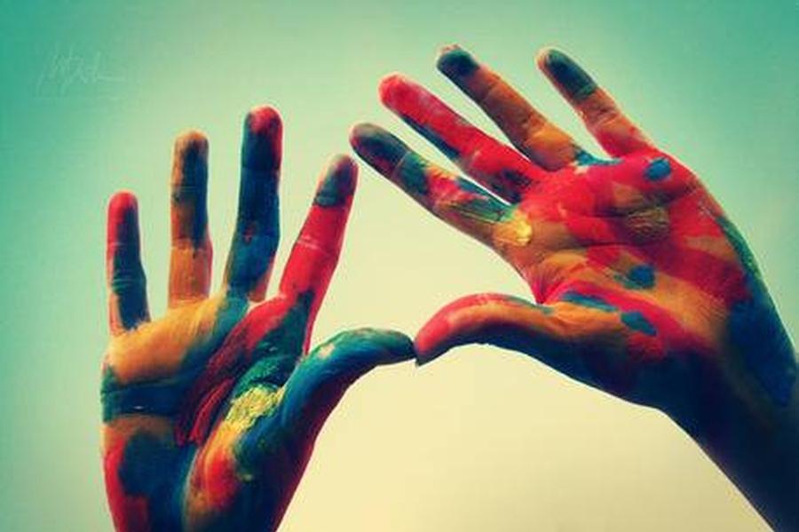 Zdjęcie uniesionych w górę rąk. Dłonie od wewnątrz pomalowane kolorowymi farbami w nieregularne wzory