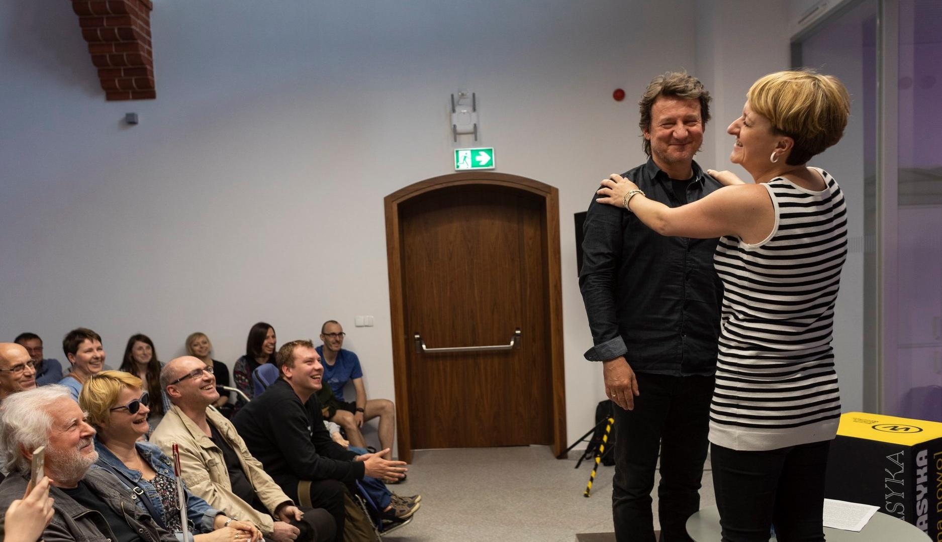 Po prawej niewidoma uczestniczka Europejskiej Nocy Literatuyr 2020 na scenie z Robertem Więckiewiczem. Po lewej tłum widzów.