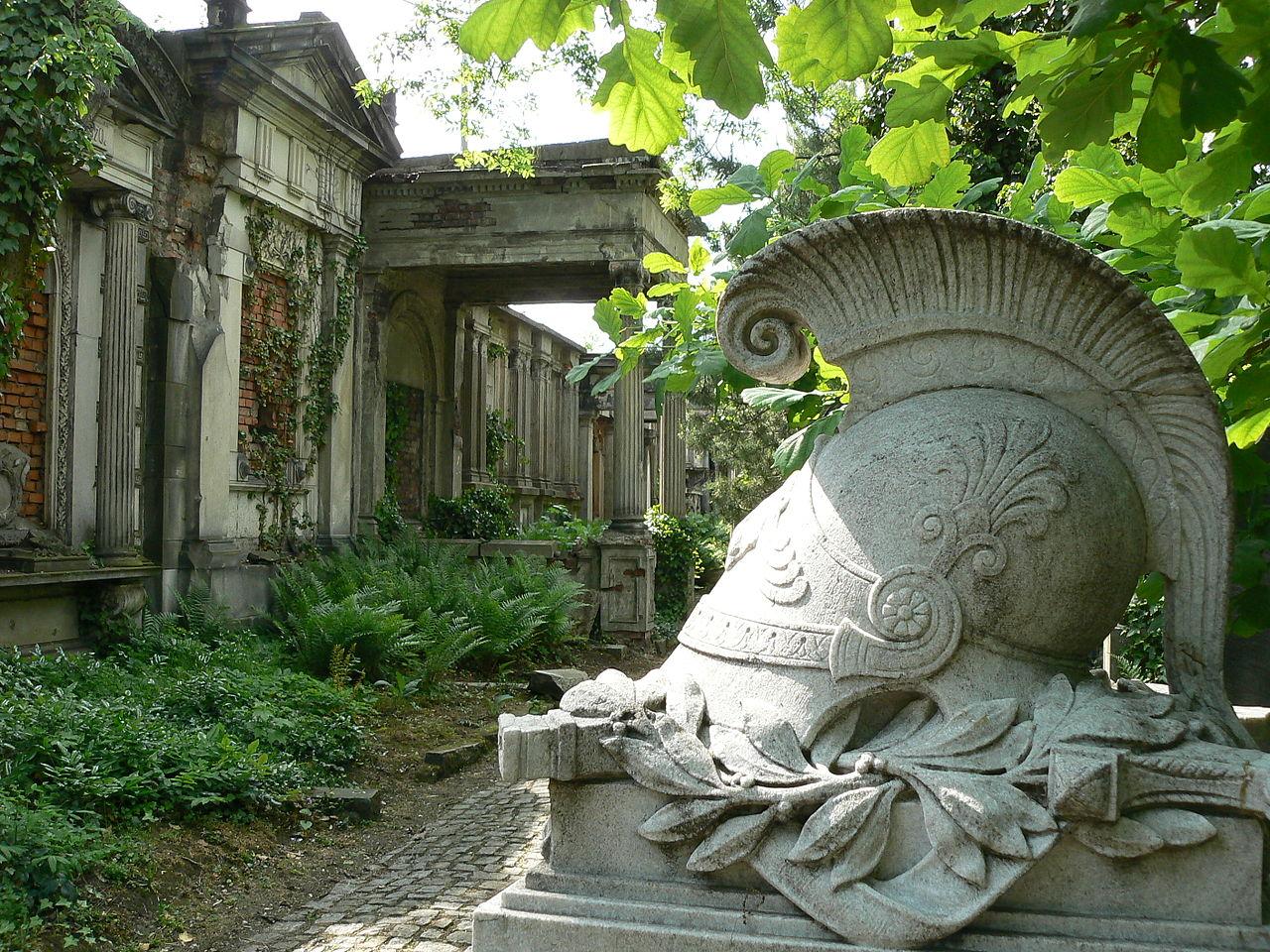 Zdjęcie ze starego cmentarza żydowskiego we Wrocławiu. Na pierwszym planie rzeźba nagrobna w kształcie hełmu starożytnego greckiego żołnierza. W tle grobowce rodzinne - klasycystyczne budynki z kolumnami.