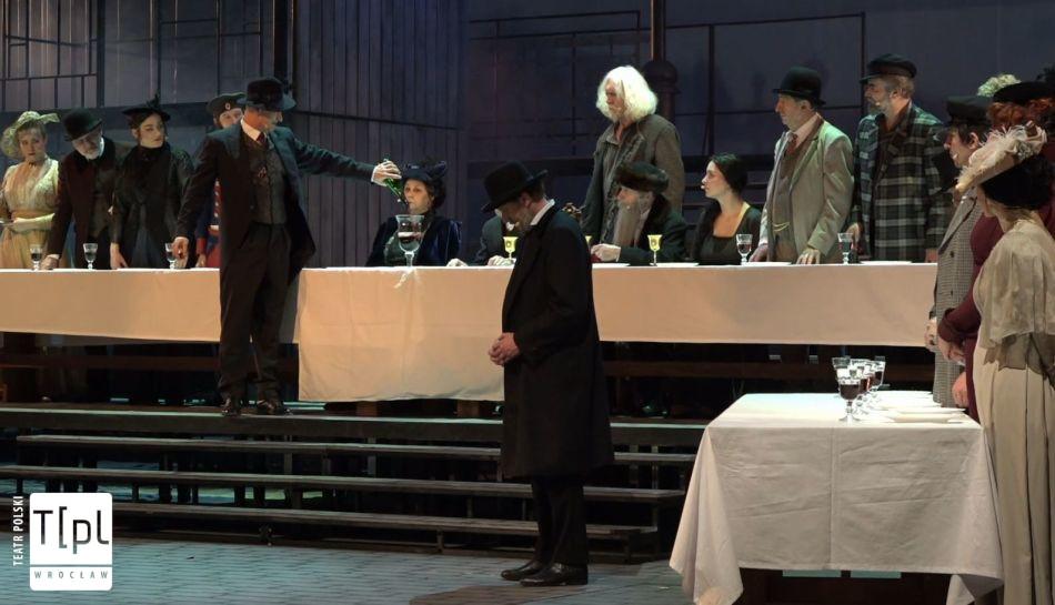 """Scena ze spektaklu """"Zmierzch - Świtem"""". Aktorzy siedzą za stołem przykrytym białym obrusem. Jeden z nich stoi i nalewa wino do wielkiego"""