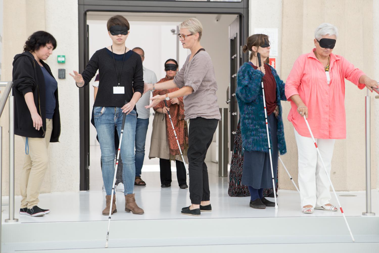 Grupa pracowników instytucji kultury podczas szkolenia z dostępności. Na oczach mają czarne opaski, a w rękach białe laski.