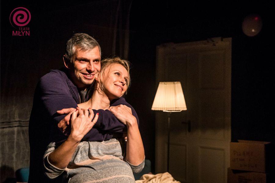 """Scena ze spektaklu """"Niedzielne popołudnie"""". W ciemnym pokoju na łóżku mężczyzna z czułością obejmuje ciężarną kobietę."""