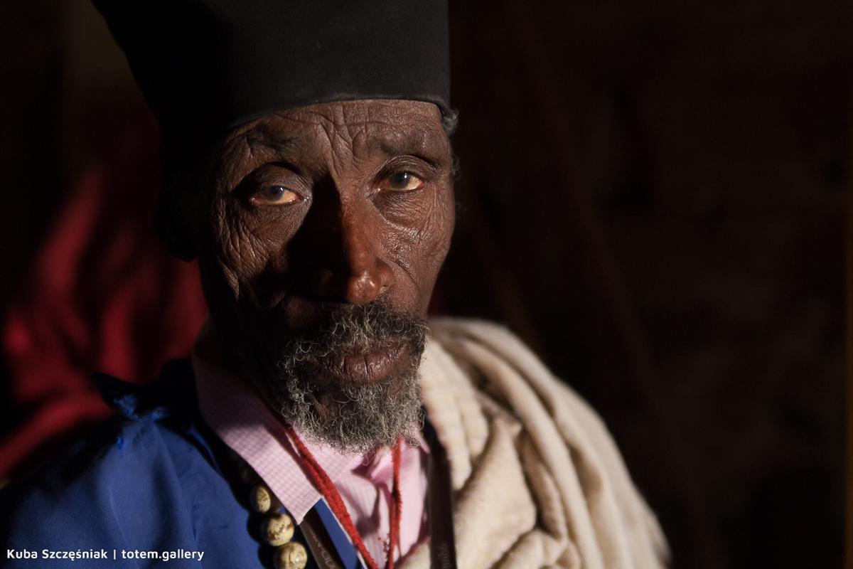 Ciemnoskóry mężczyzna z brodą i zmarszczakami na twarzy w etiopskim stroju i nakryciu głowy
