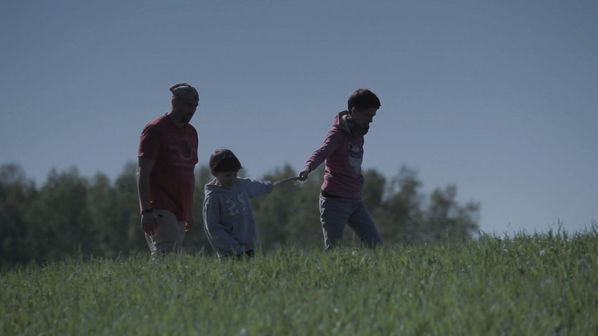 Joanna, Piotr i syn Jaś idą przez łąkę. Dziecko idzie w środku, Joanna trzyma je za rękę