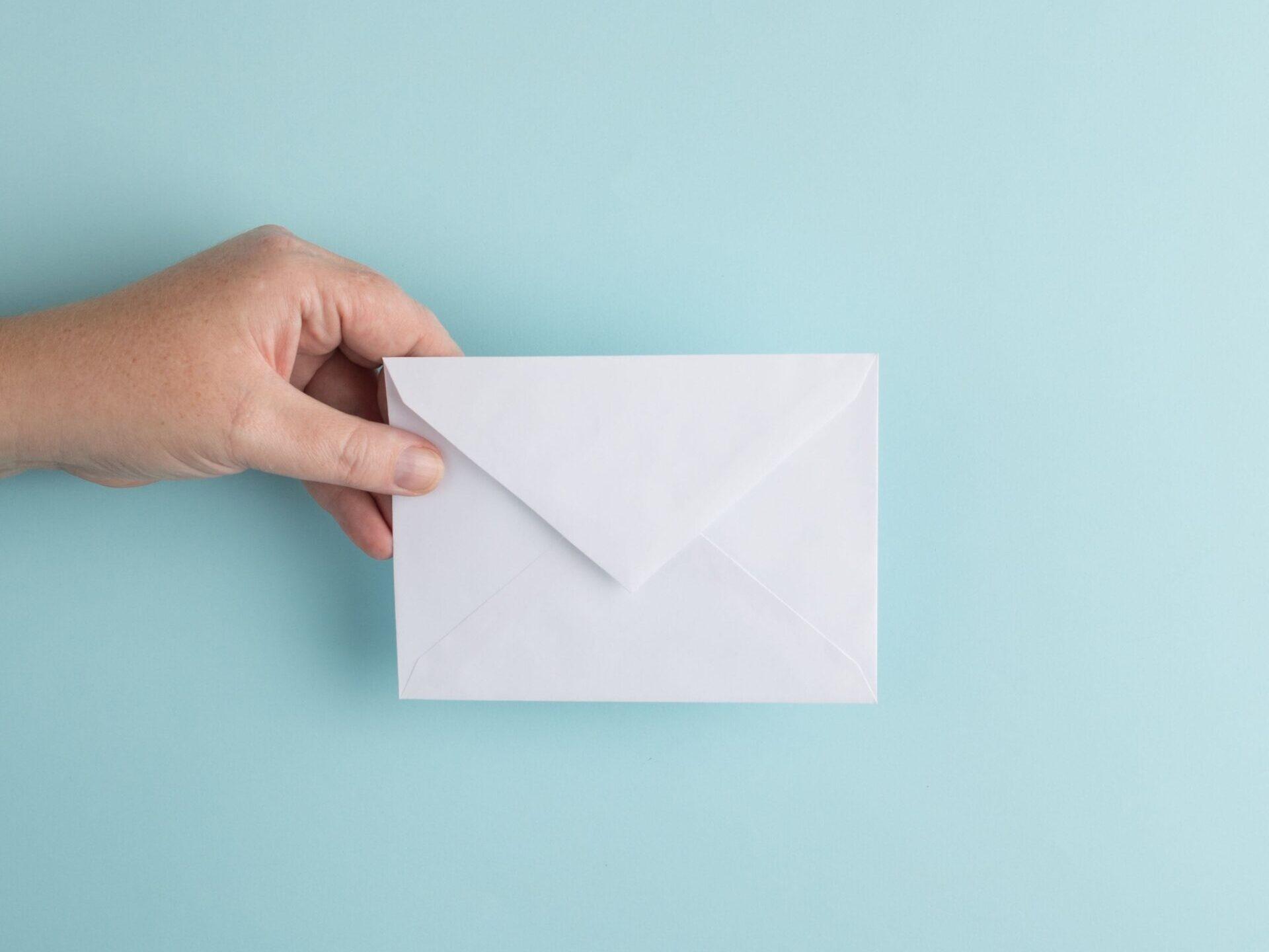 na niebieskim tle kobieca dłoń trzyma białą kopertę na listy