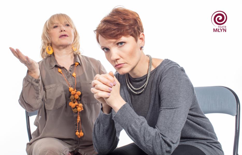 Dwie kobiety siedzące na krześle, jedna jest zamyślona, ma ręce złożone, druga coś opowiada ręce unosi w górę