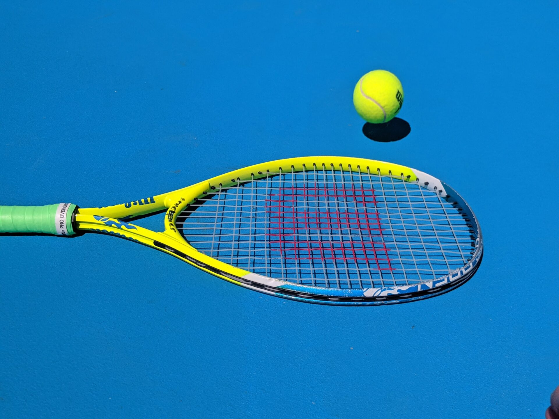 Rakieta i piłka do tenisa na niebieskim tle