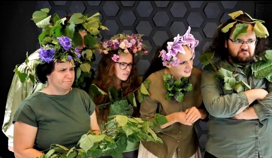 """Kadr z filmu """"Listek z nieba"""". 5 aktorów na kogoś patrzy. Ubrani są w brązowo-zielone koszule, na głowach mają wianki z kwiatów i liści"""