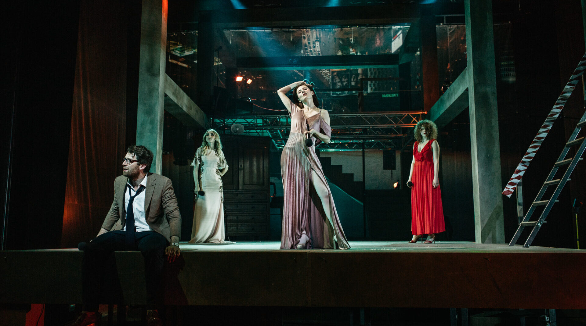 Scena. Aktorki w eleganckich sukienkach trzymają w dłoniach mikrofony. Przed nimi mężczyzna w okularach i w marynarce siedzi na krawędzi sceny.