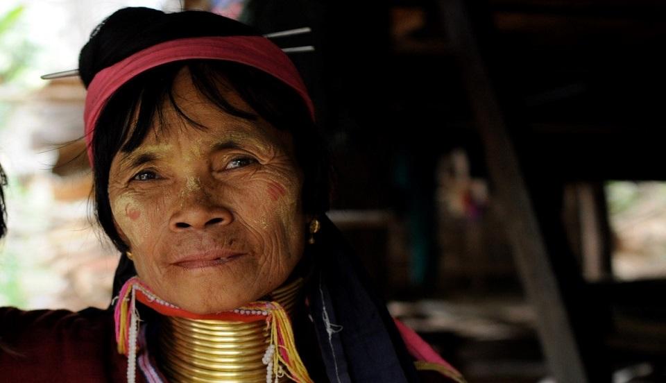 Zbliżenie starszej kobiety z birmańskiego plemienia Kajan. Kobieta ma szyi ma metalowe obręcze, na głowie opaskę. Patrzy w dal